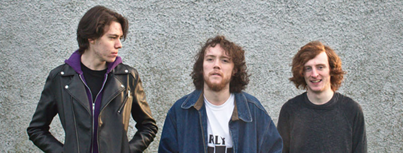 Happy Out: three young white men with long hair wearing casual clothes stand in front of a plain grey wall.