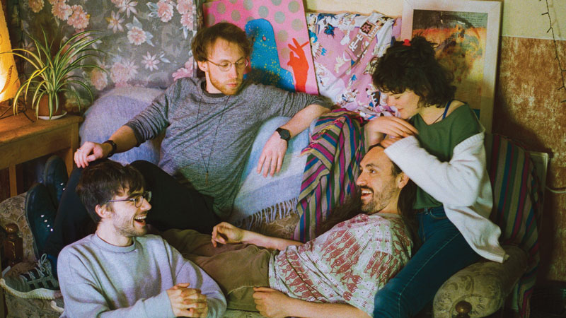 The band Lunch Machine: three young men and a woman wearing casual clothes lounge together happily on a boho sofa.