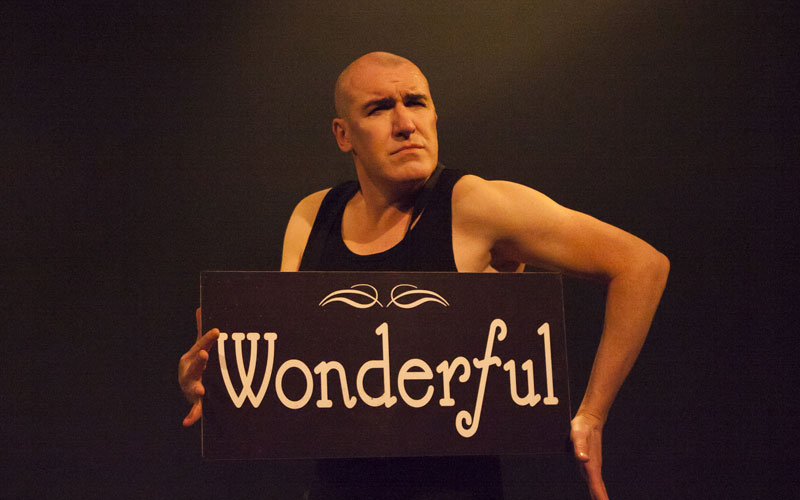 Actor Pat Kinevane holds a sign with 'Wonderful' written on it, in a scene from his play 'Silent.