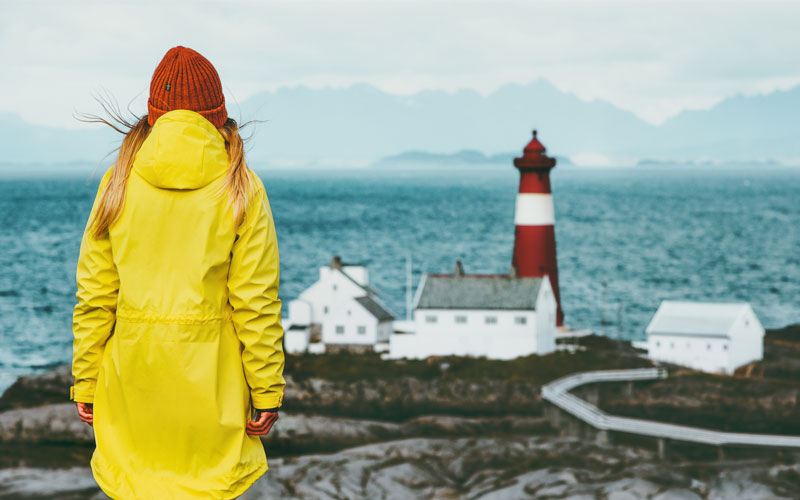 Image is on a girl wearing a bright yellow yellow rain coat and a red wooden hat looking across a rugged coastal seascape with a red and white lighthouse in the distance.