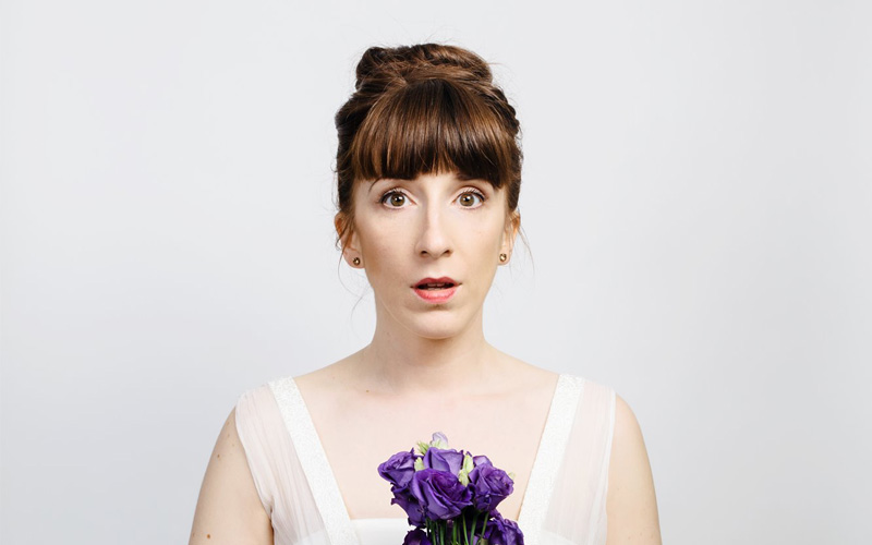 A startled young woman wearing a white wedding dress, holding a bouquet of purple flowers.