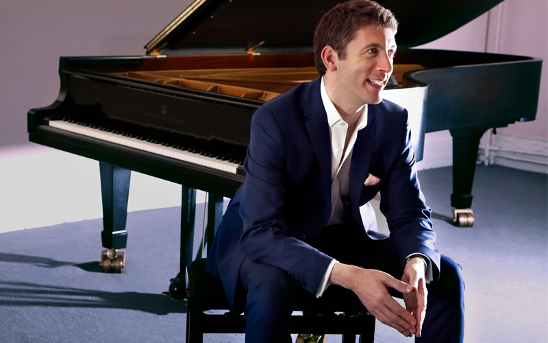A smartly dressed young man sits in front of a grand piano