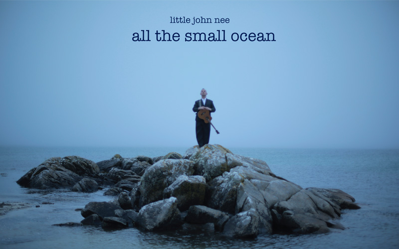 A middle aged man wearing a dark suit and holding a guitar stands on a rocky outcrop in a calm, grey blue ocean.